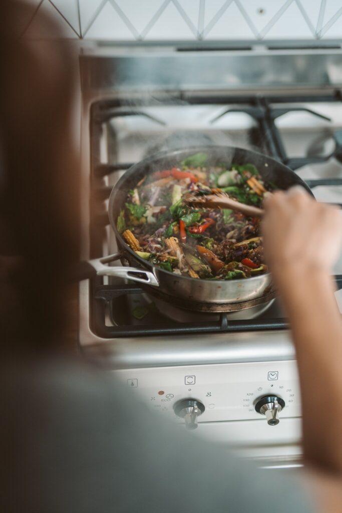 Iemand die aan het koken is in een zwarte pan