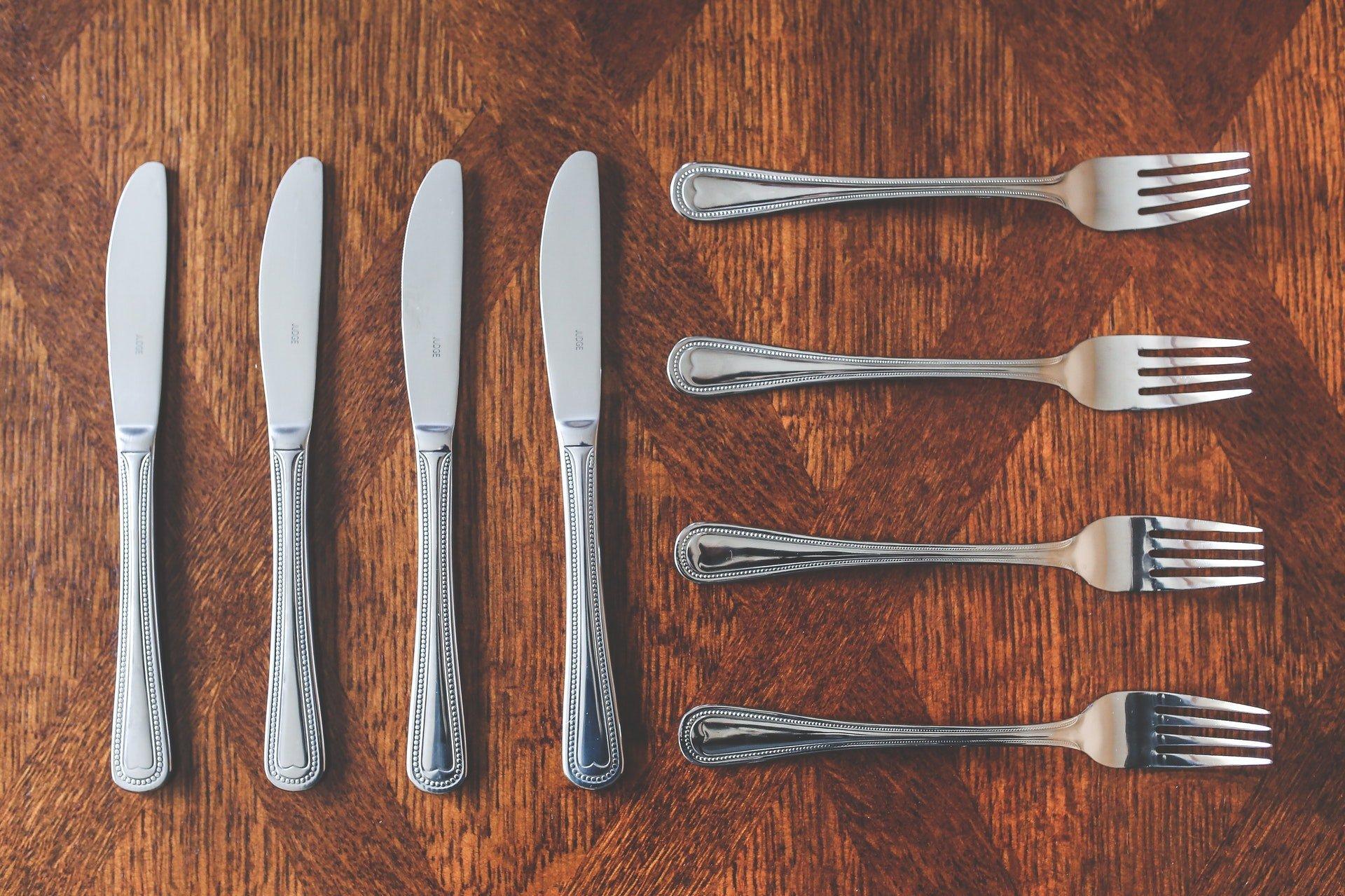 Een viertal zilveren messen en vorken op een houten tafel