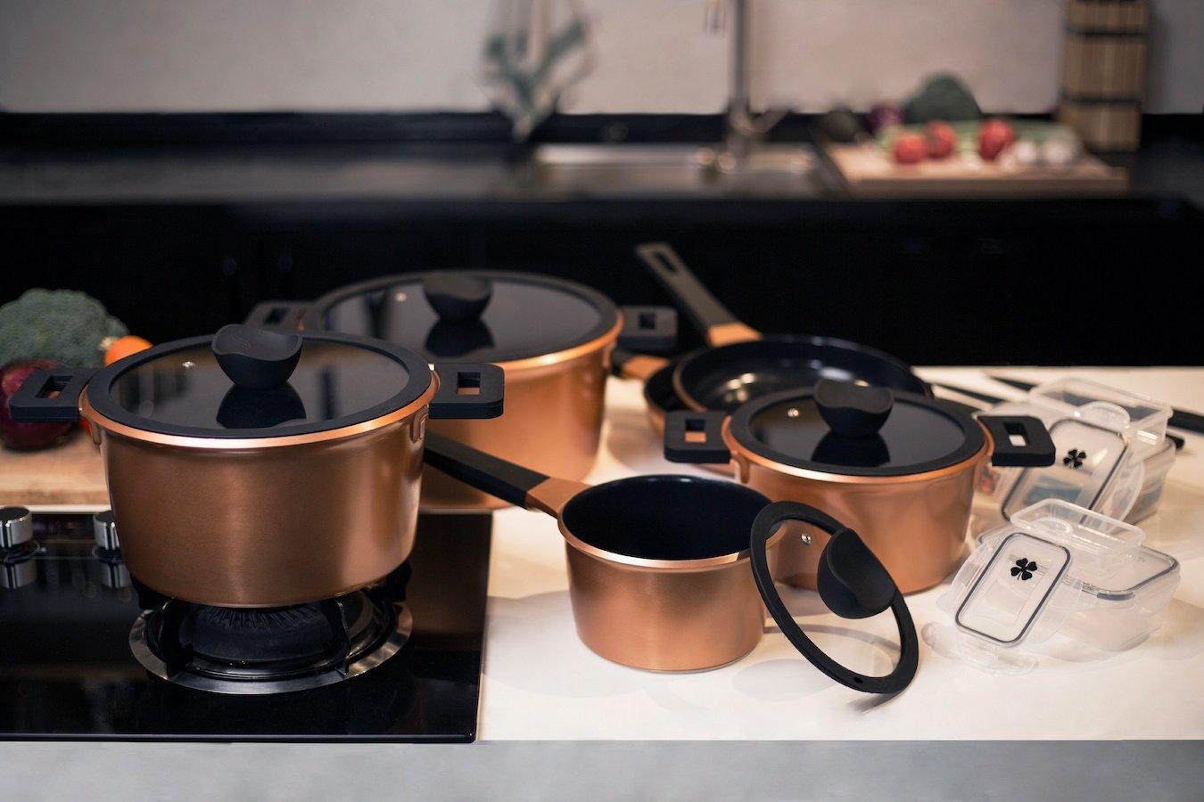 Prachtige koperen pannenset staande op een een keukenplaat en fornuis