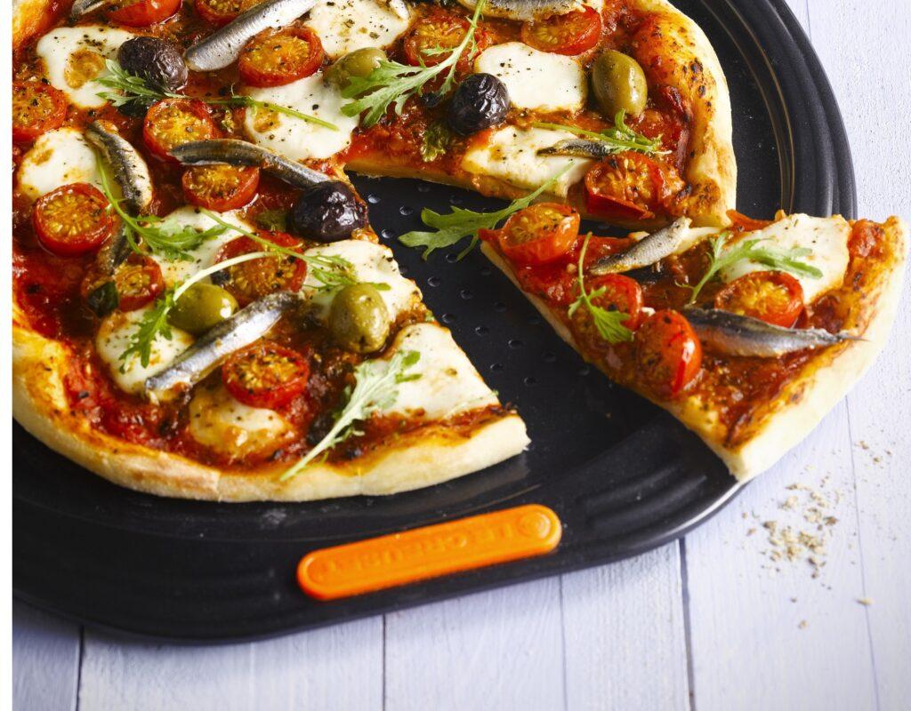 Warme pizza op een pizzaplaat van Le Creuset